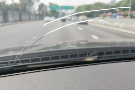 Perspectiefmening van gebarsten autovoorruit of windscherm van binnenuit voertuig terwijl het drijven