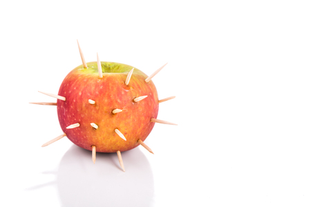 Conceptual of apple with thorns denote sharp pain when bite, on white background