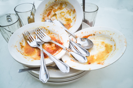Pile of dirty oily messy plates, glass, cups, fork spoons after meal Stock Photo