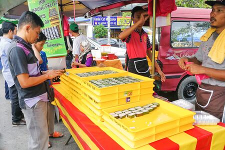 pelita: KUALA LUMPUR, MALAYSIA, June 2, 2017: Muslim shopper buying sweet desserts from street stall vendor for breaking fast or iftar
