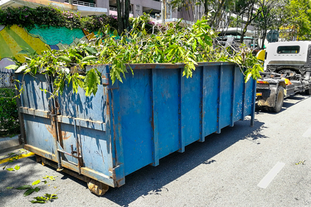 Garbage container latch with truck full of garden refuse, woods, chopped trees for disposal Stockfoto