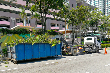 Garbage container latch with truck full of garden refuse, woods, chopped trees for disposal Stock fotó
