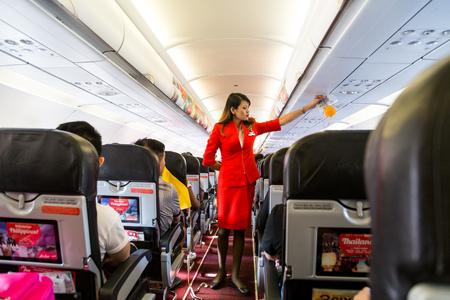 KUALA LUMPUR, Malásia, 8 de junho de 2017: a anfitriã da Airasia demonstra procedimentos de segurança para os passageiros antes da decolagem do vôo.