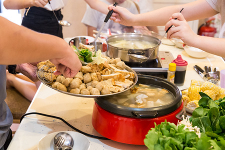 Hand adding ingredients into Asian steamboat pot dinner meal