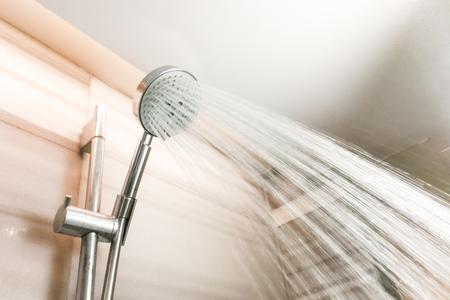 Duschkopf mit den auffrischenden Wassertröpfchen, die hinunter in Badezimmer sprühen