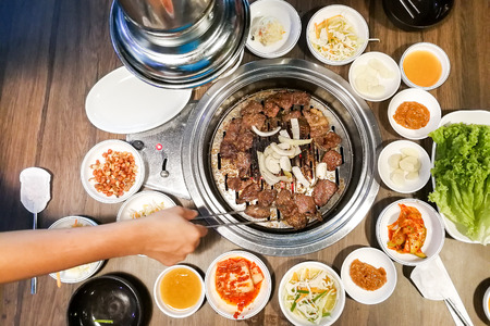 Person barbecue beef on bbq pit during korean meal set in restaurant