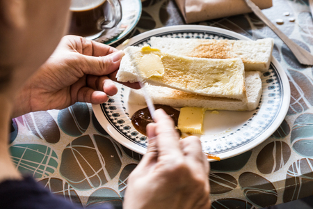 kopitiam: Series of person applying delicious butter and kaya to steamed bread, popular breakfast to be taken with coffee in Malaysia