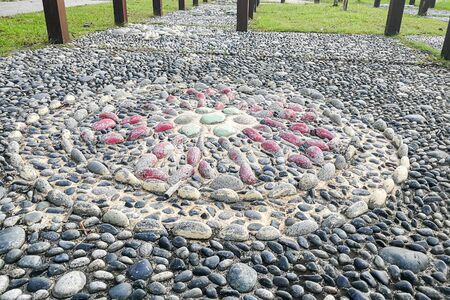promotes: Close-up on pebble stones at foot reflexology park. Walking on them stimulates pressure points, promotes health and well-being.