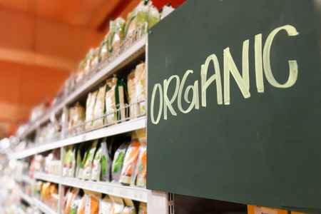 supermarket: Organic food signage on modern supermarket grocery aisle to appeal to healthy lifestyle shoppers Stock Photo