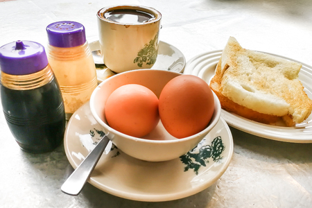 Asian traditional breakfast combination of half boiled eggs, toast bread with butter and kaya and coffee Foto de archivo
