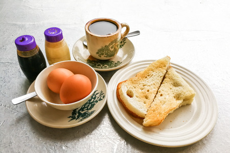 Asian traditional breakfast combination of half boiled eggs, toast bread with butter and kaya and coffee Standard-Bild