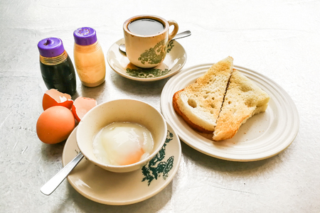Asian traditional breakfast combination of half boiled eggs, toast bread with butter and kaya and coffee Stock Photo