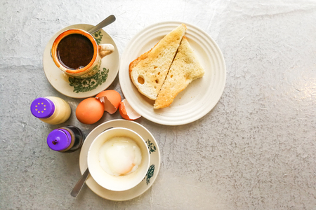Aziatische traditionele ontbijt combinatie van halfgekookte eieren, toastbrood met boter en kaya en koffie