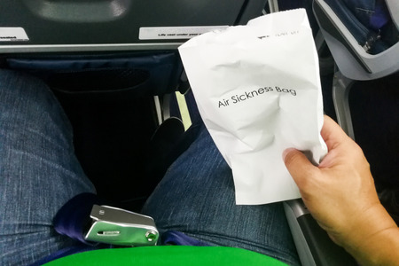 Airsick nauseous person holding the air sickness vomit bag prepared to vomit Stock Photo