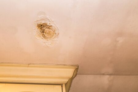 Roof leakages results ugly corrosion and damage on plaster ceiling Stock Photo