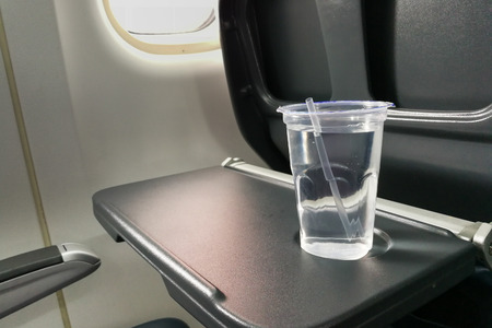 Disposable refreshing mineral water on table in air plane cabin to hydrate passenger