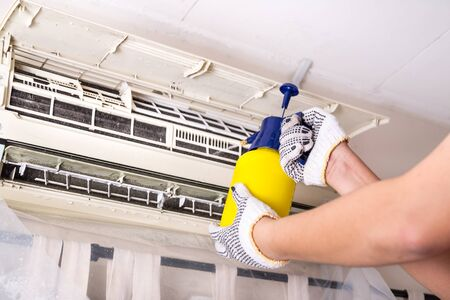 Technician spraying chemical water onto air conditioner coil to clean and disinfect Archivio Fotografico