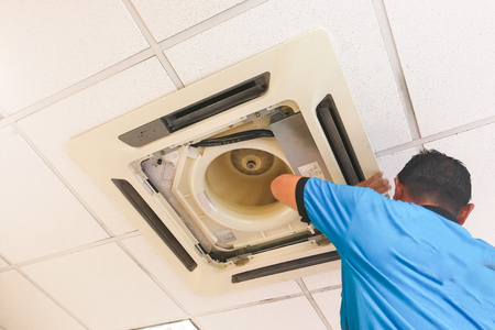 Technician servicing, maintaining and fixing a ceiling air conditioner cartridge in office