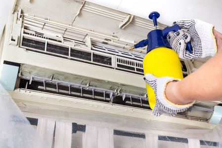 Technician spraying chemical water onto air conditioner coil to clean and disinfect Banque d'images