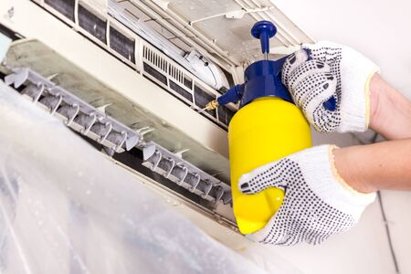 Technician spraying chemical water onto air conditioner coil to clean and disinfect Stockfoto