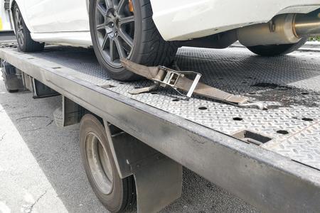 Pneumatico auto assicurato con cintura per la sicurezza sul camion di rimorchio a pianale Archivio Fotografico - 89176955