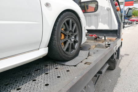 Broken down auto vehicle car towed onto flatbed tow truck with hook and chain Zdjęcie Seryjne