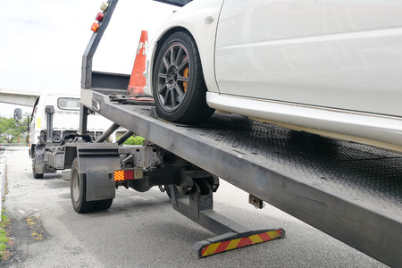 Broken down auto vehicle car towed onto flatbed tow truck with hook and chain Stock Photo