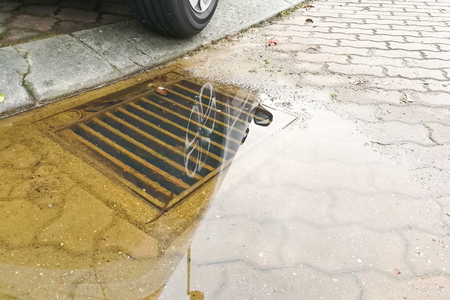 Waterlogged on street after rain due to badly clogged drainage system