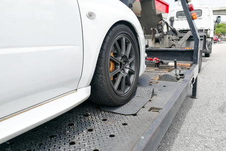 Broken down auto vehicle car towed onto flatbed tow truck with hook and chain Standard-Bild