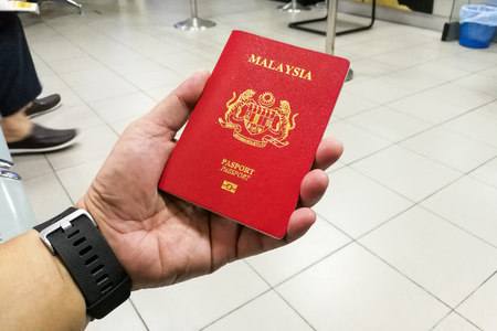 Person holding Malaysia international passport.