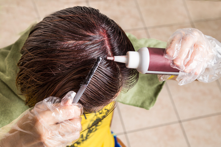 Woman attempting to apply chemical hair color onto scalp.  Self help solution. Stock Photo
