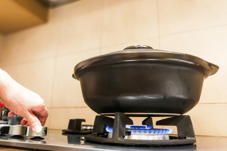 Ceramic clay pot on gas fire generated stove.  Not suitalbe material as clay is porous. Stock Photo