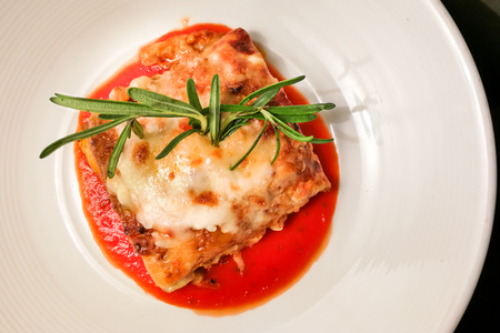 Closeup overhead view of fine dining italian lasagna served on elegant style