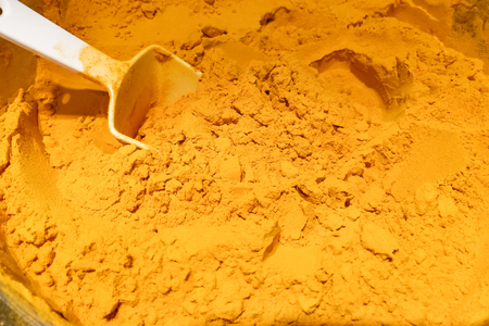 Pile of organic turmeric powder with ladle
