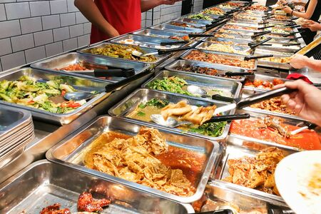 People picking variety of food at Chinese economy rice stall in Malaysia