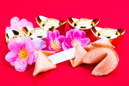 Chinese fortune cookies with decorative gold nuggets, plum blossom flowers and blank predictive label on red background