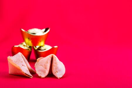 Chinese fortune cookies with decorative gold nuggets on red background Stock Photo