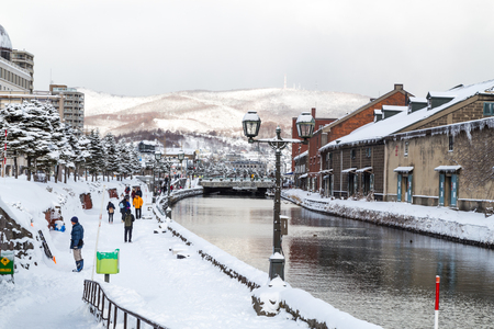 Otaru, Japan, January 28, 2018:  Otaru canal with nostalgic buidings is popular tourist destination in Hokkaido.  Featured here the canal during winter with thick snow.
