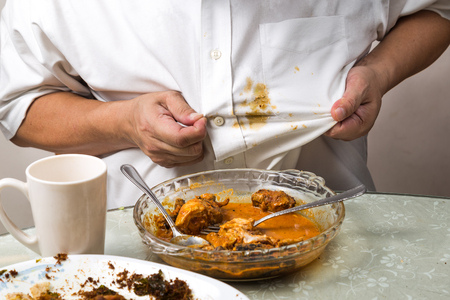 Person accidently spilled curry stain onto white shirt and reacted with frustration. Archivio Fotografico