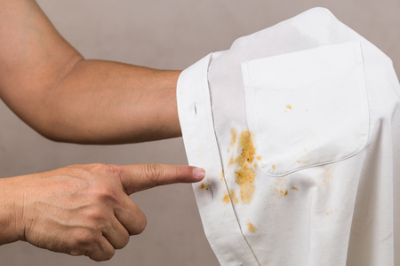 Frustrated person pointing to spilled curry stain on white shirt
