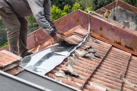 Asian worker replacing roof tiles and metal sheets of old residential building roof Stockfoto