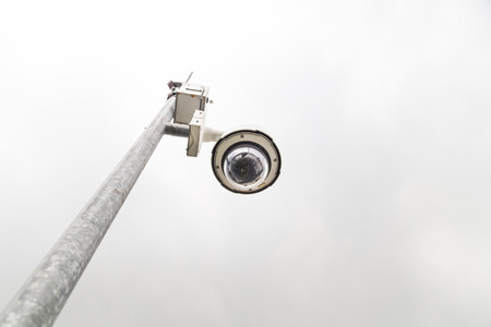 Outdoor security surveillance cctv camera against gloomy overcast sky with copy space Stock Photo