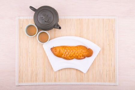 Fish shaped mooncake pastries for Chinese mid-autumn celebration served with Chinese tea