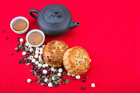 Mid-Autumn festival Chinese mooncake  with ingredients and tea on red background