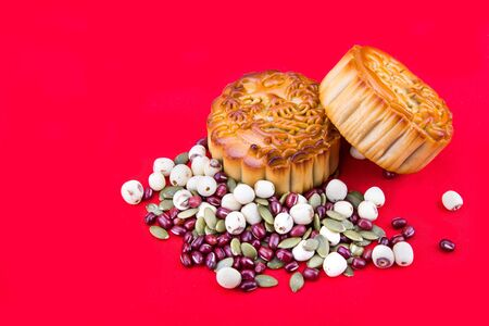 Close-up on mooncake with ingredients, pastries for Chinese mid-autumn festive in red background 版權商用圖片