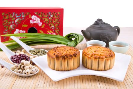 Mid Autumn festival Chinese mooncake  with ingredients and tea on red background