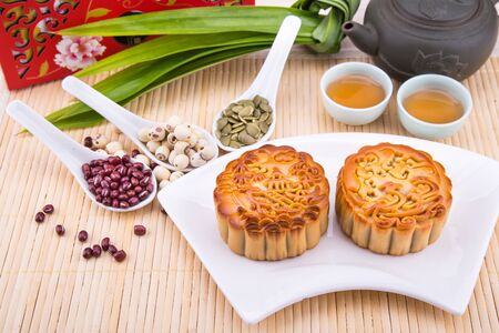 Mooncake for Chinese mid-autumn festival celebration, wih ingredients and tea on table top 版權商用圖片
