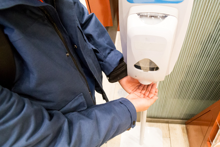 Person cleaning hand with anti-bacterial hand disinfectant sanitizer dispenser in public mall in Japan