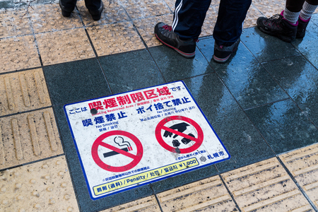 Japan authorities strict on smoking and littering at restricted area.  Featured here warning and penalty signage on street pavement.