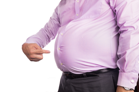 Man in shirt pointing own unhealthy big belly with visceral or subcutaneous fats. Pose health risk. Stockfoto